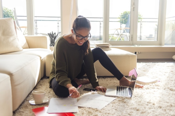 Smiling young teen girl sitting with laptop and papers learning how to invest in living room